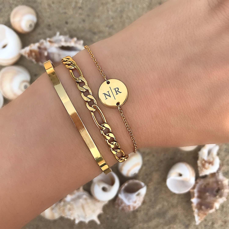 Gouden armbandjes om de pols met mix en match op het strand