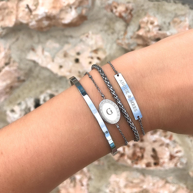 Zilveren graveerbare armband om de pols samen met een leuke gravering