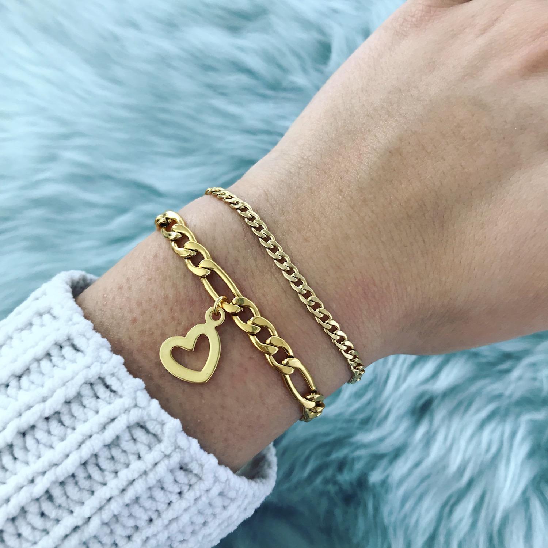 Vrouw draagt gouden schakelarmbandjes combinatie
