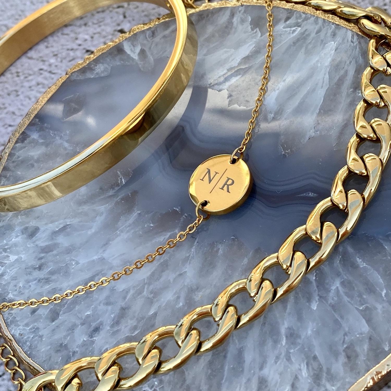 Gouden mix van armbanden op blauwe stenen ondergrond