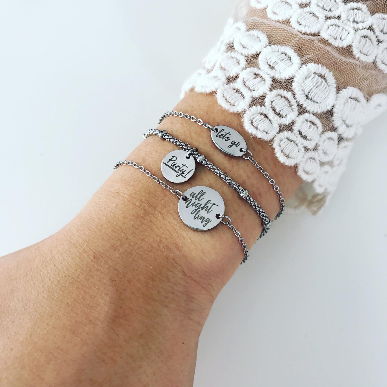 Drie zilveren quote armbandjes met witte kanten top