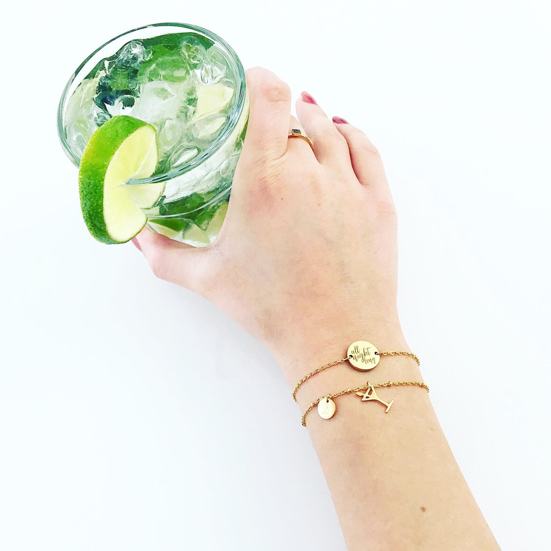 Pols met twee gouden quote armbandjes en cocktail