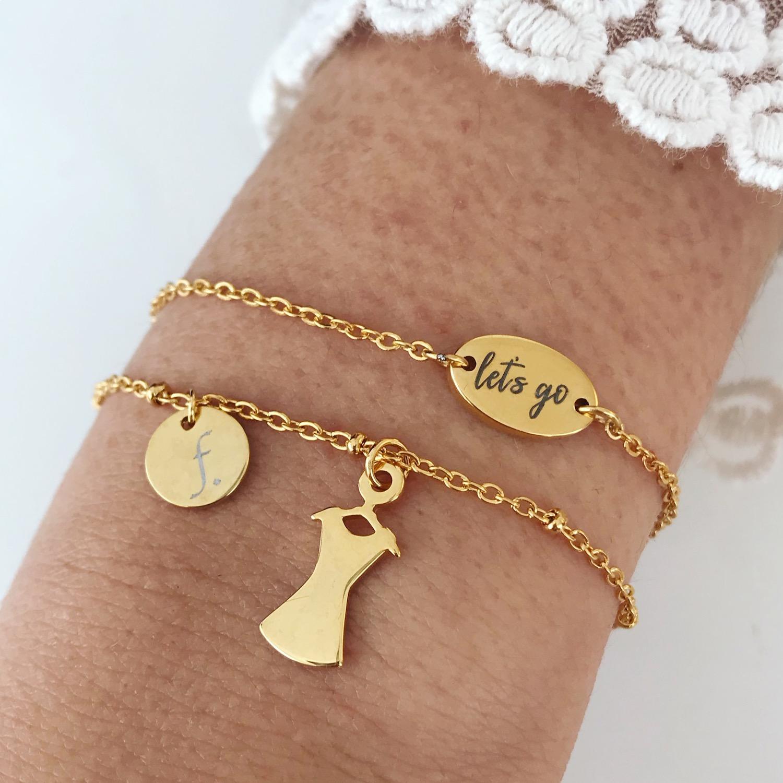 Twee gouden party armbandjes met quote en jurkje