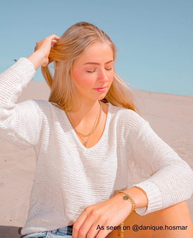 Influencer aan het strand met gouden sieradenlook