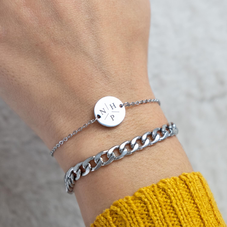 Pols met twee zilveren armbandjes initialen en cocktail