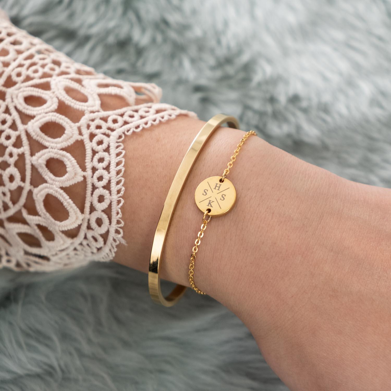 Pols met gouden armbandjes initialen en open bangle