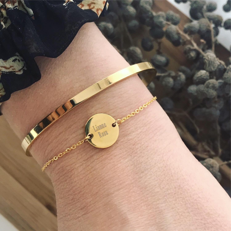 Pols met twee gouden armbandjes graveerbaar en bangle