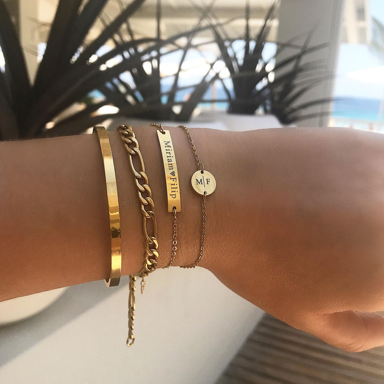 Mooie mix van gouden armbanden om de pols met gravering