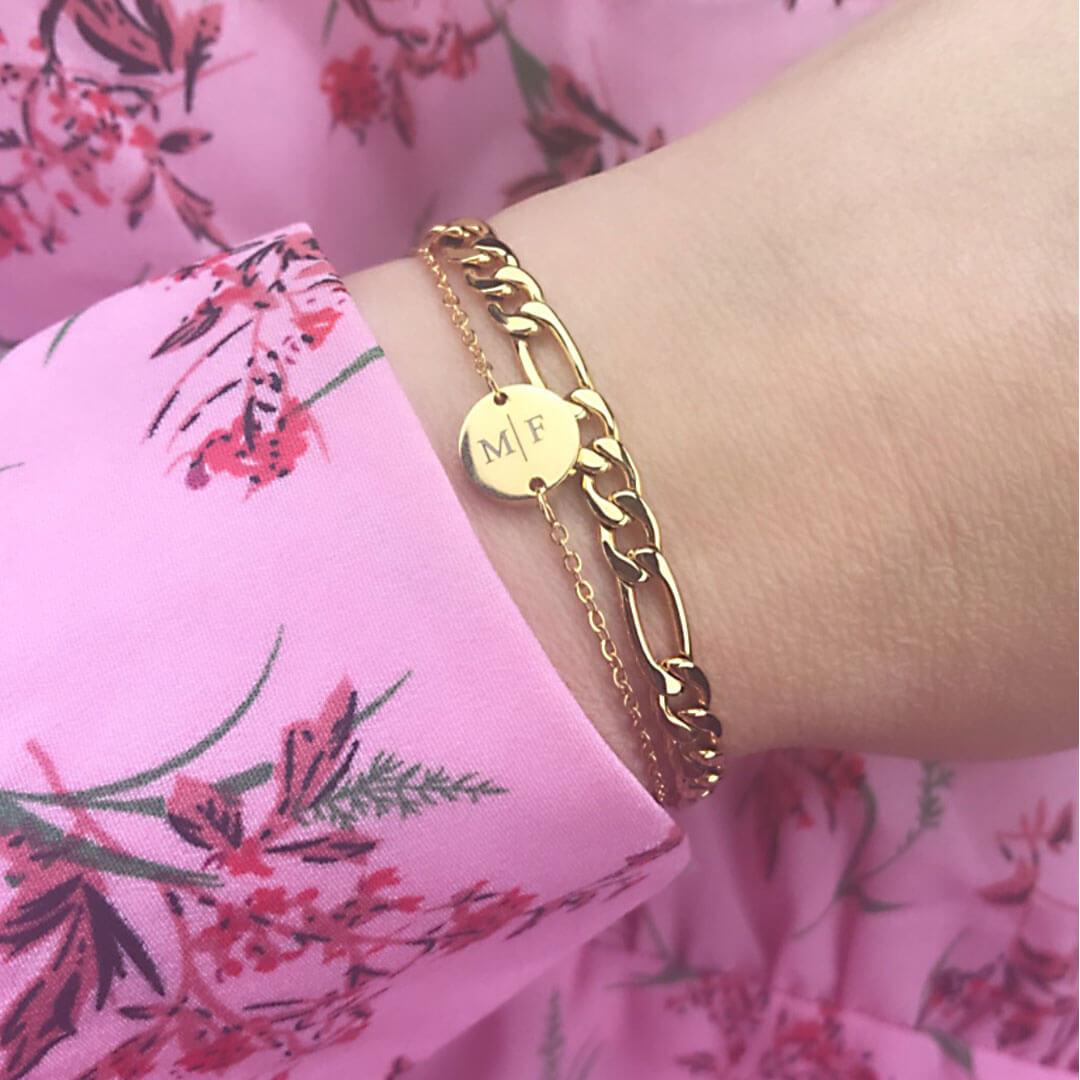 Vrouw draagt initialen en schakel armband om pols