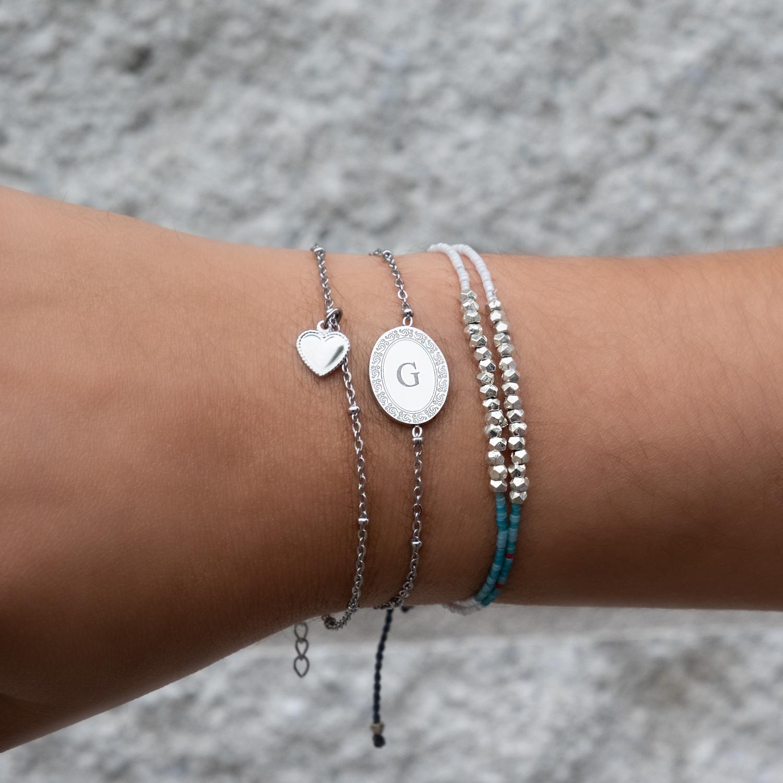 Vrouw draagt graveerbare zilveren armband met initialen