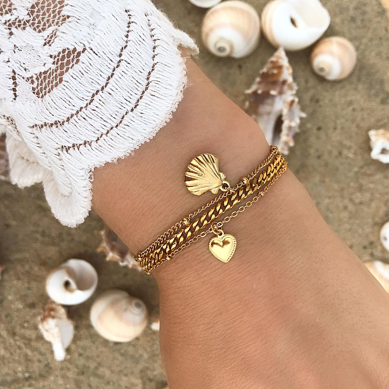 Schakelarmbandje in het goud om de pols op het strand