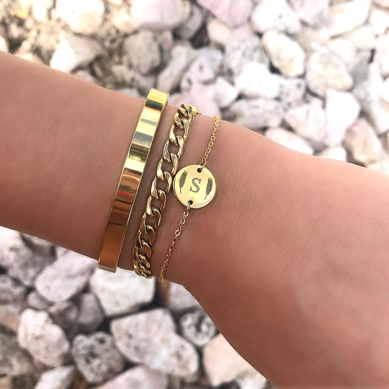 Gouden bangle om de pols samen met een graveerbare armband om de pols