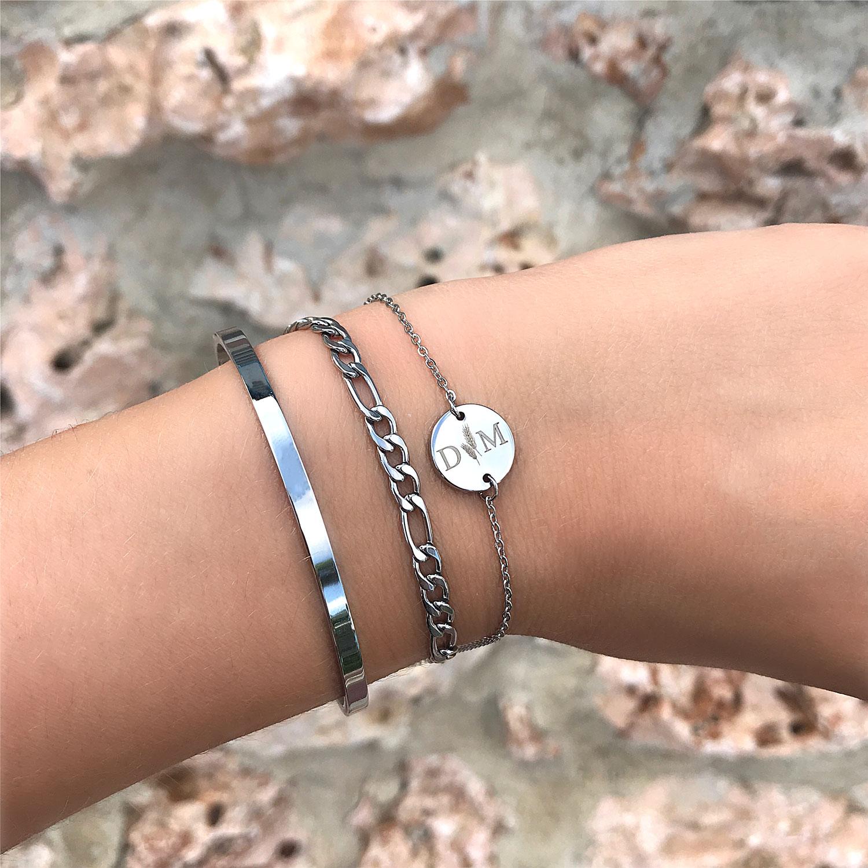 Zilverkleurige armbandjes om de pols met gravering en minimalistische bangle