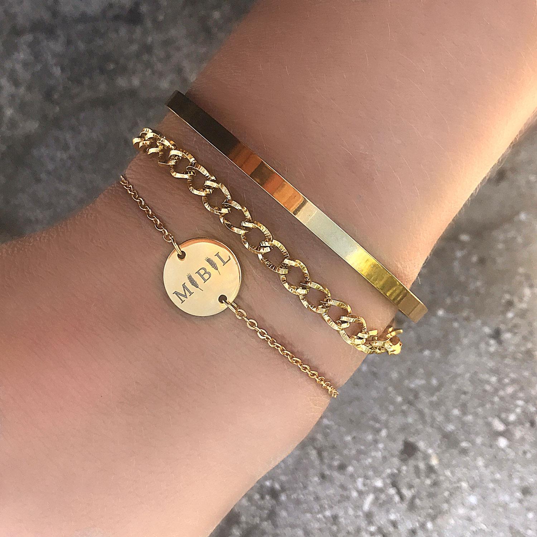 Gouden schakelarmband om de pols met een graveerbare armband