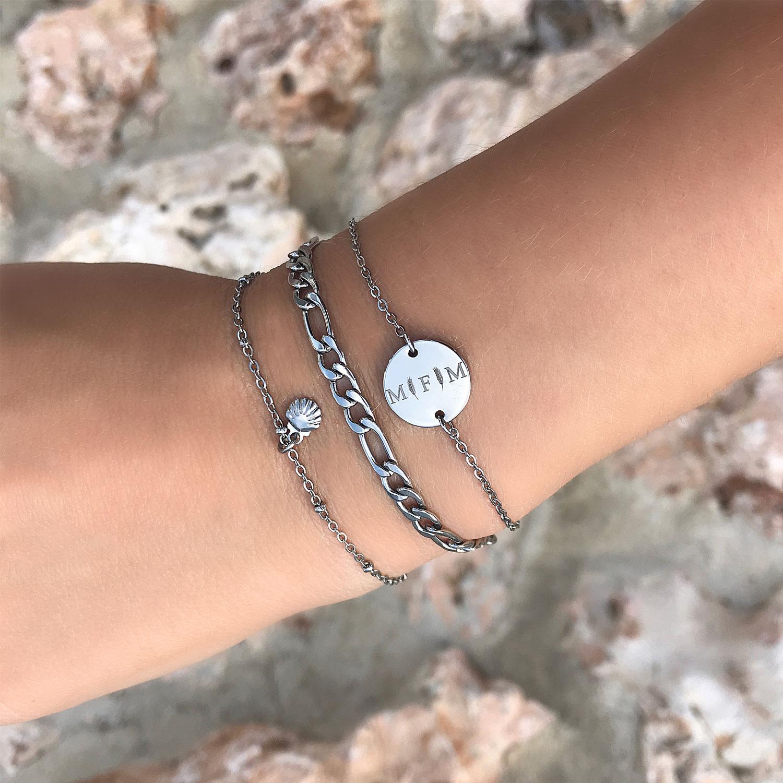 Zilveren armband met schelpje om de pols samen met gravering