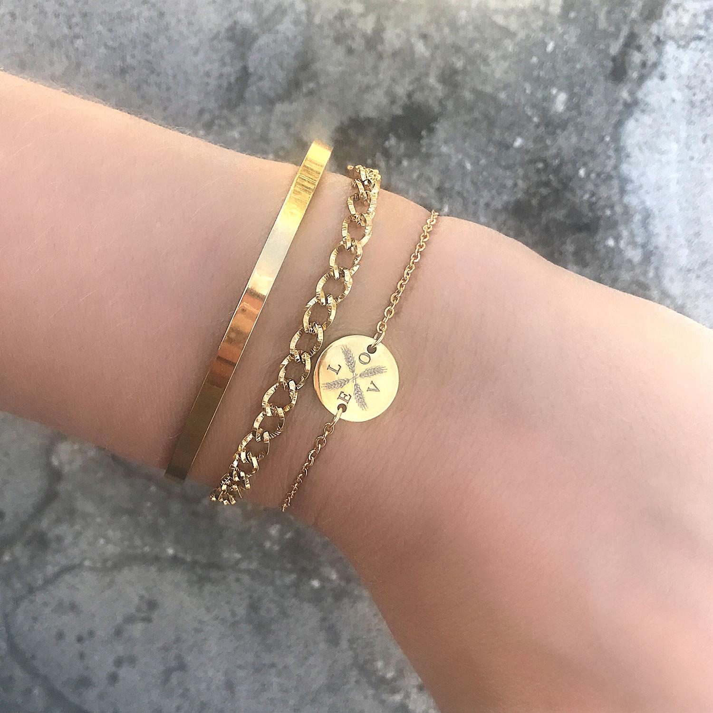 Gouden armbanden om de pols met bangle en schakelarmband
