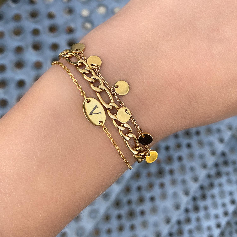 Vrouw draagt leuke mix van gouden armbandjes om de pols