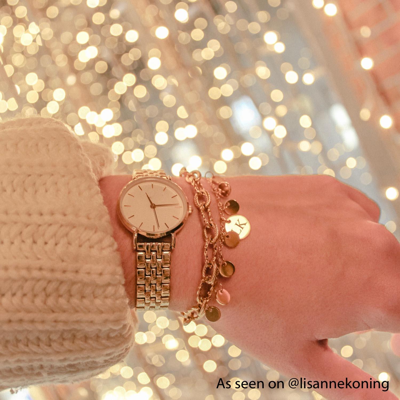 Gouden armbandjes om de hand van een influencer