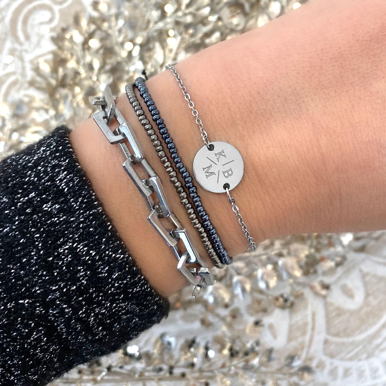 Vrouw draagt een trendy zilveren schakelarmband om de pols