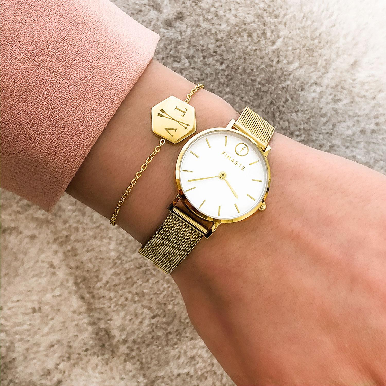 Gouden sieraden om de pols met een mooi horloge erbij