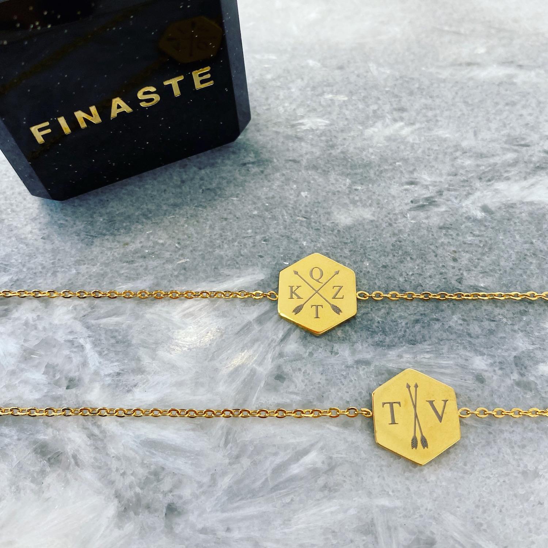 Twee gouden armbandjes met letters en sieradendoosje