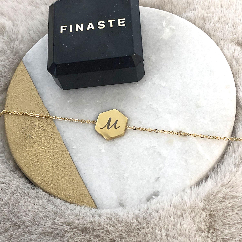 Gouden letter armband met sierletters en een sieradendoosje