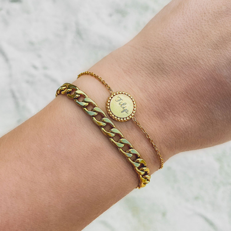 Gouden armband met gravering om de pols en een schakelarmband