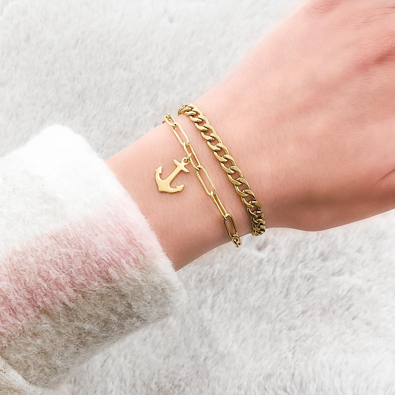 Gouden schakelarmband om de pols met een hangertje