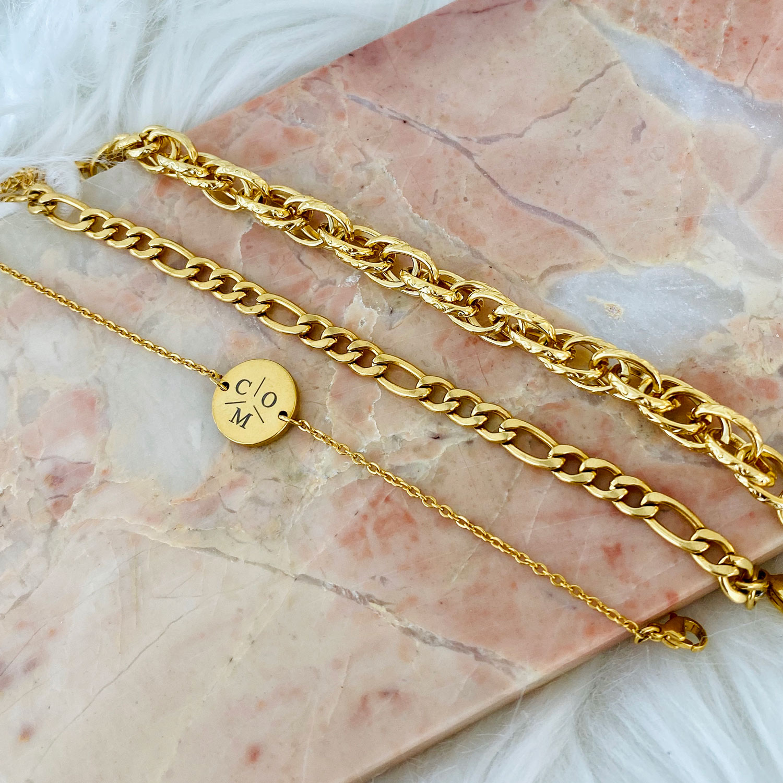 Gouden schakelarmbanden op marmeren ondergrond