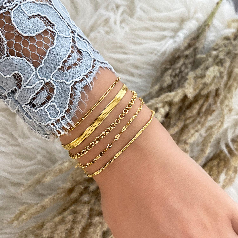 Gouden armbandjes mix om pols bij vrouw
