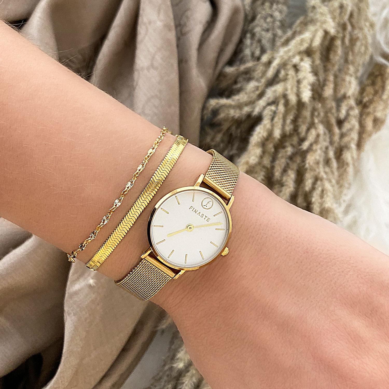 Gouden armbandjes met horloge om pols