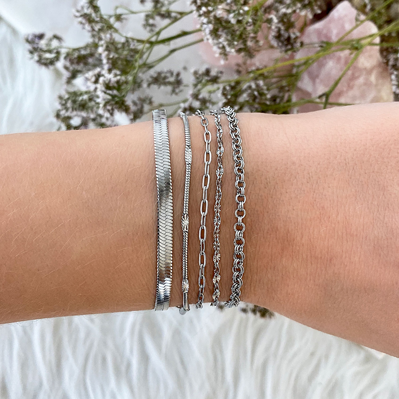 Meerdere zilveren armbanden met elkaar gecombineerd