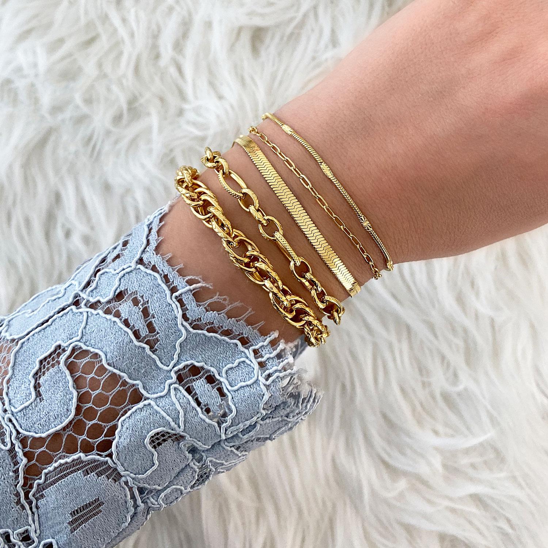 Vrouw draagt gouden armbanden combinatie om haar pols