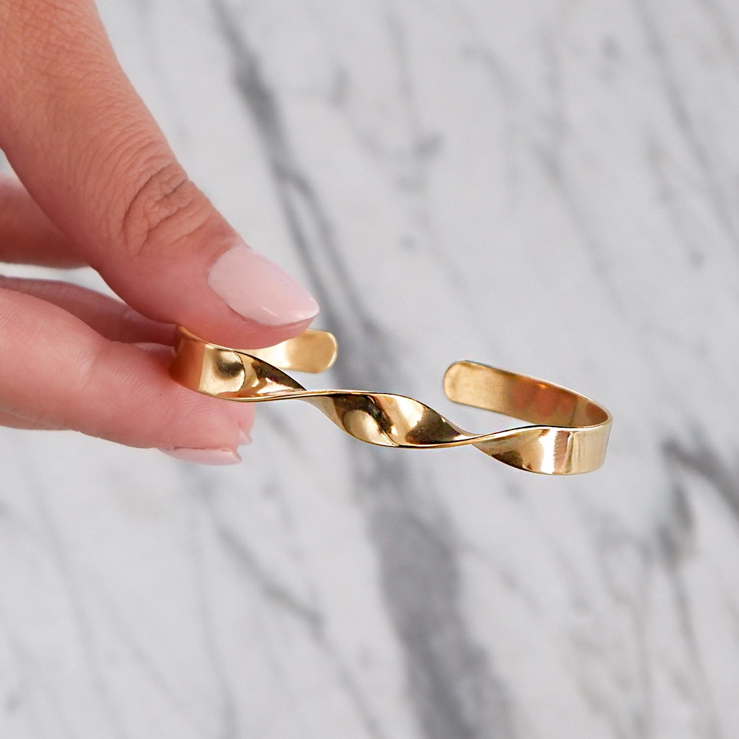 Mooie goudkleurige bangle in de hand