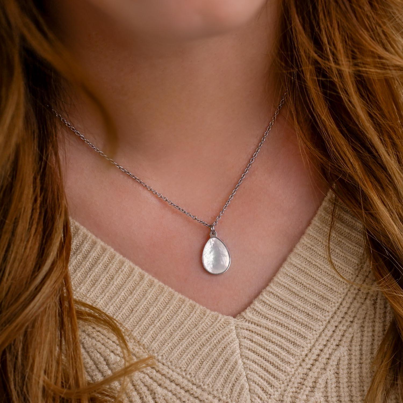 Vrouw draagt druppel pearl ketting om hals