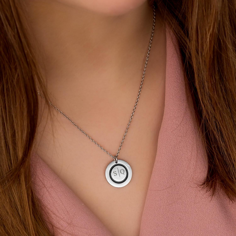 Meisje draagt ketting met 2 initialen om hals
