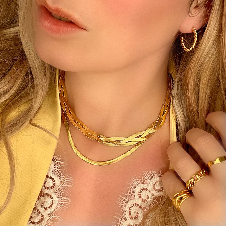 Het model draagt de mooie nieuwe platte gevlochten ketting in het goudkleurig