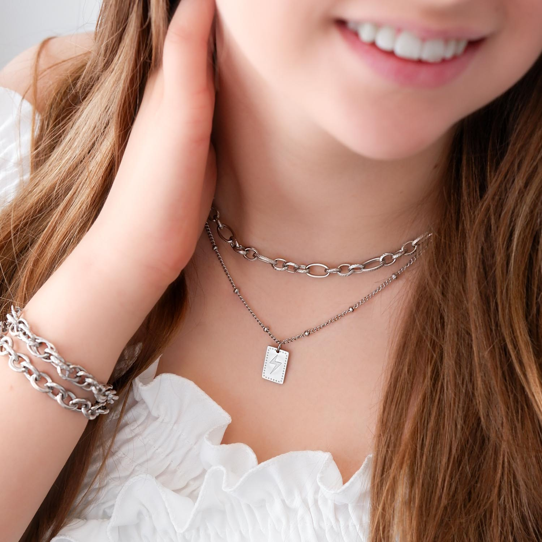 Meisje draagt mix van zilveren kettinkjes