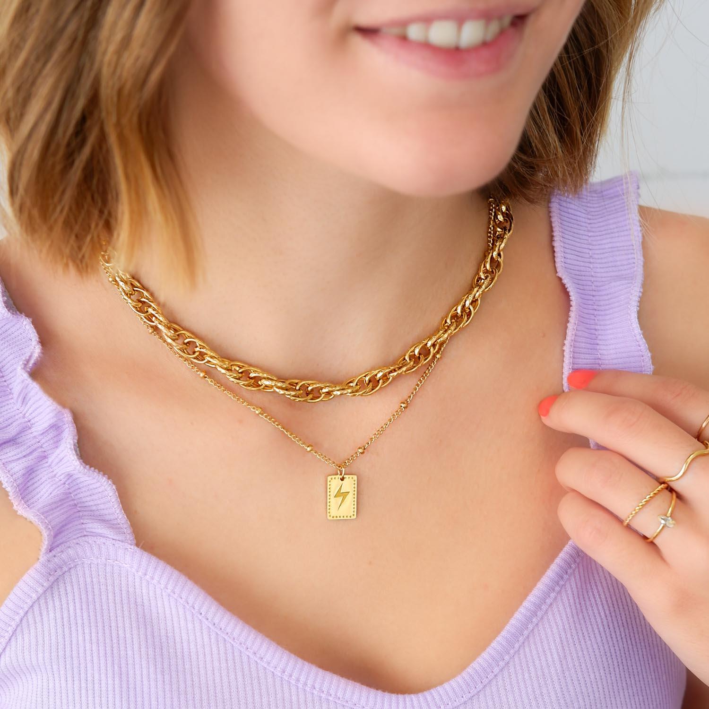 Gouden bliksem ketting bij meisje om hals