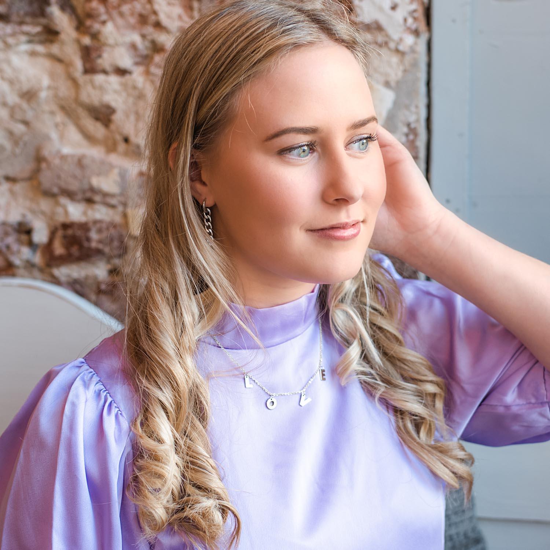 Zilveren letter ketting love om de hals bij een vrouw met blonde haren