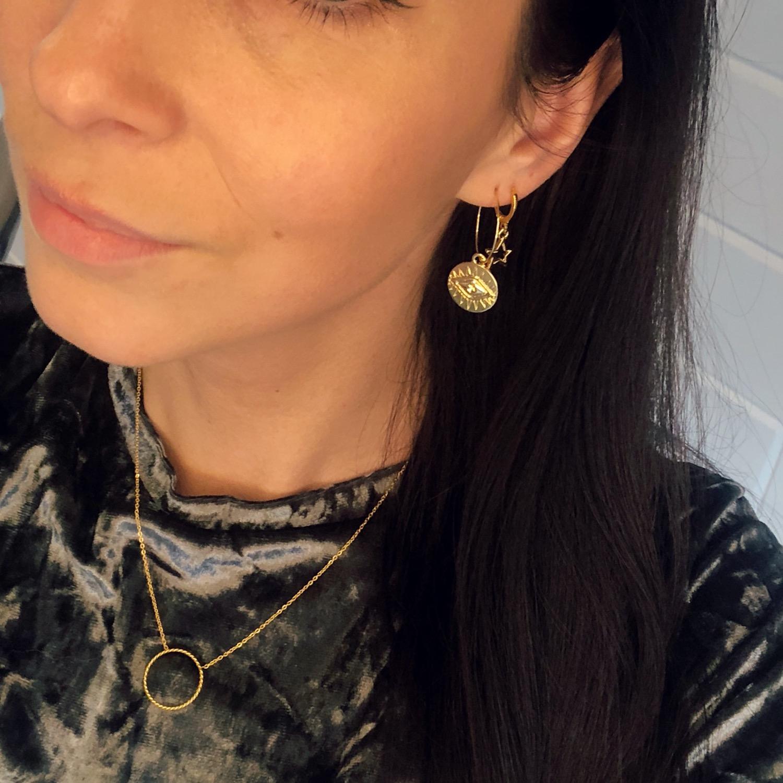 Meisje draagt gouden cirkel ketting met gouden oorbellen