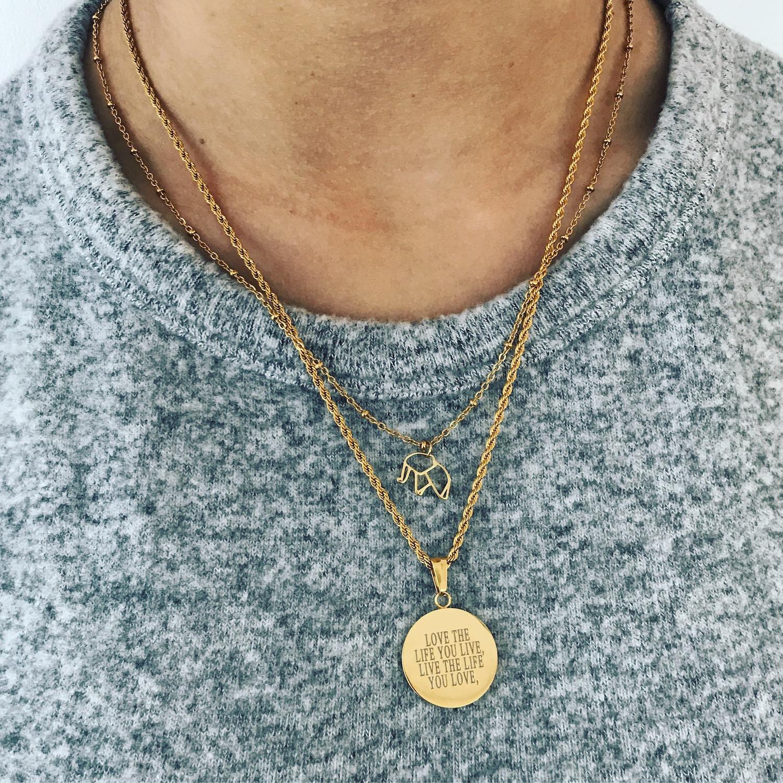 Vrouw met grijze trui draagt graveerbare gouden ketting rond van finaste