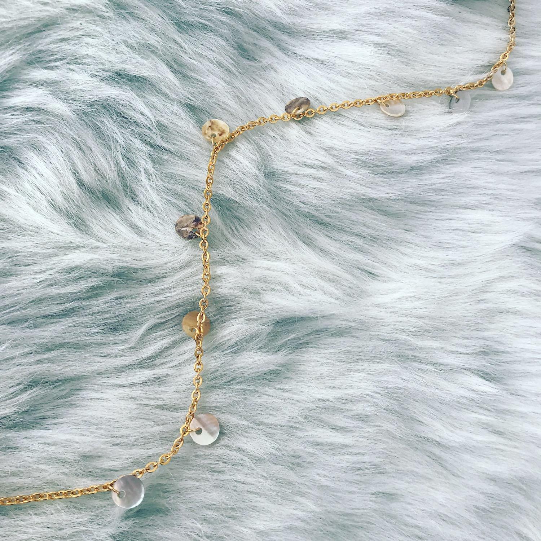 Gouden ketting met schelpjes op grijs vachtje