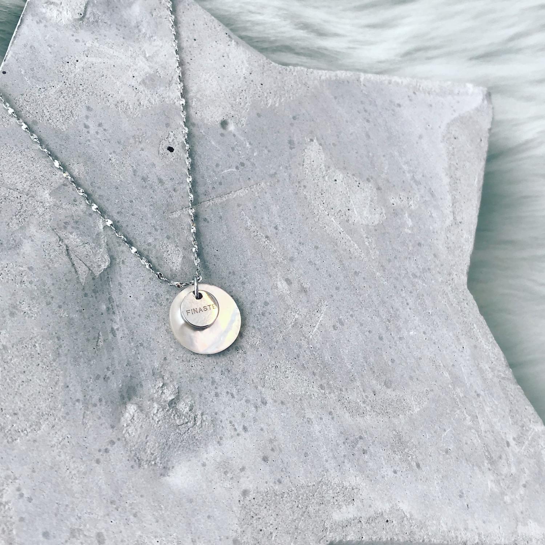 Zilveren schelpjes ketting op grijze ondergrond