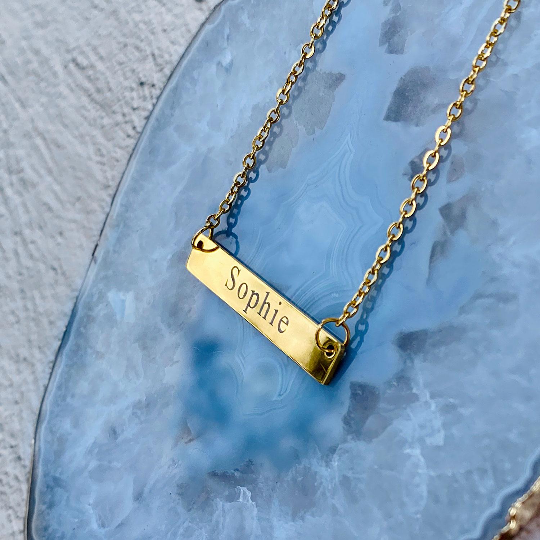 Gouden graveerbare naamketting op stenen ondergrond