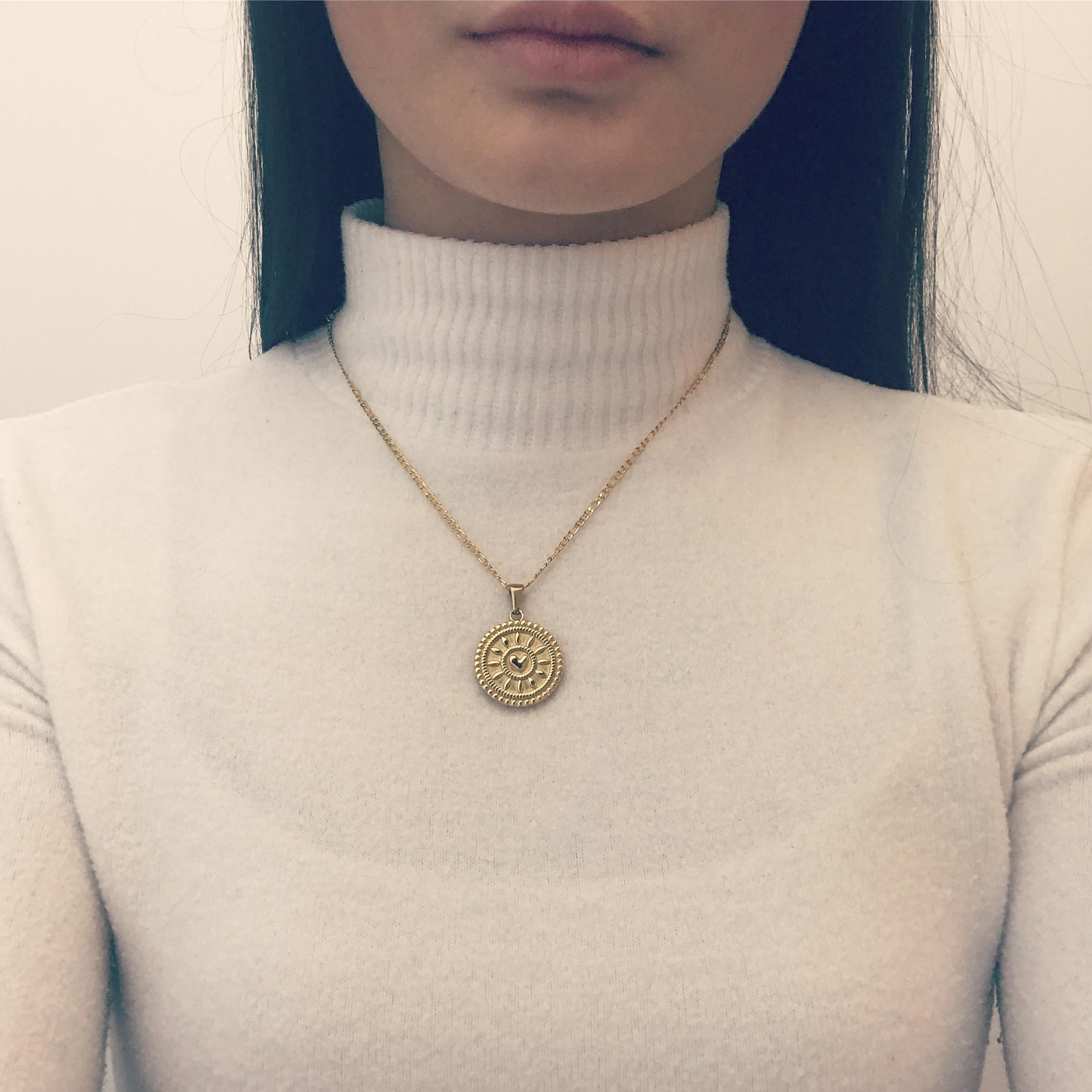 Meisje draagt een gouden ketting met grote munt en een hartje