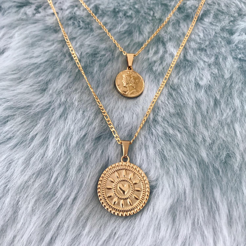 Twee gouden kettinkjes met munt op vachtje