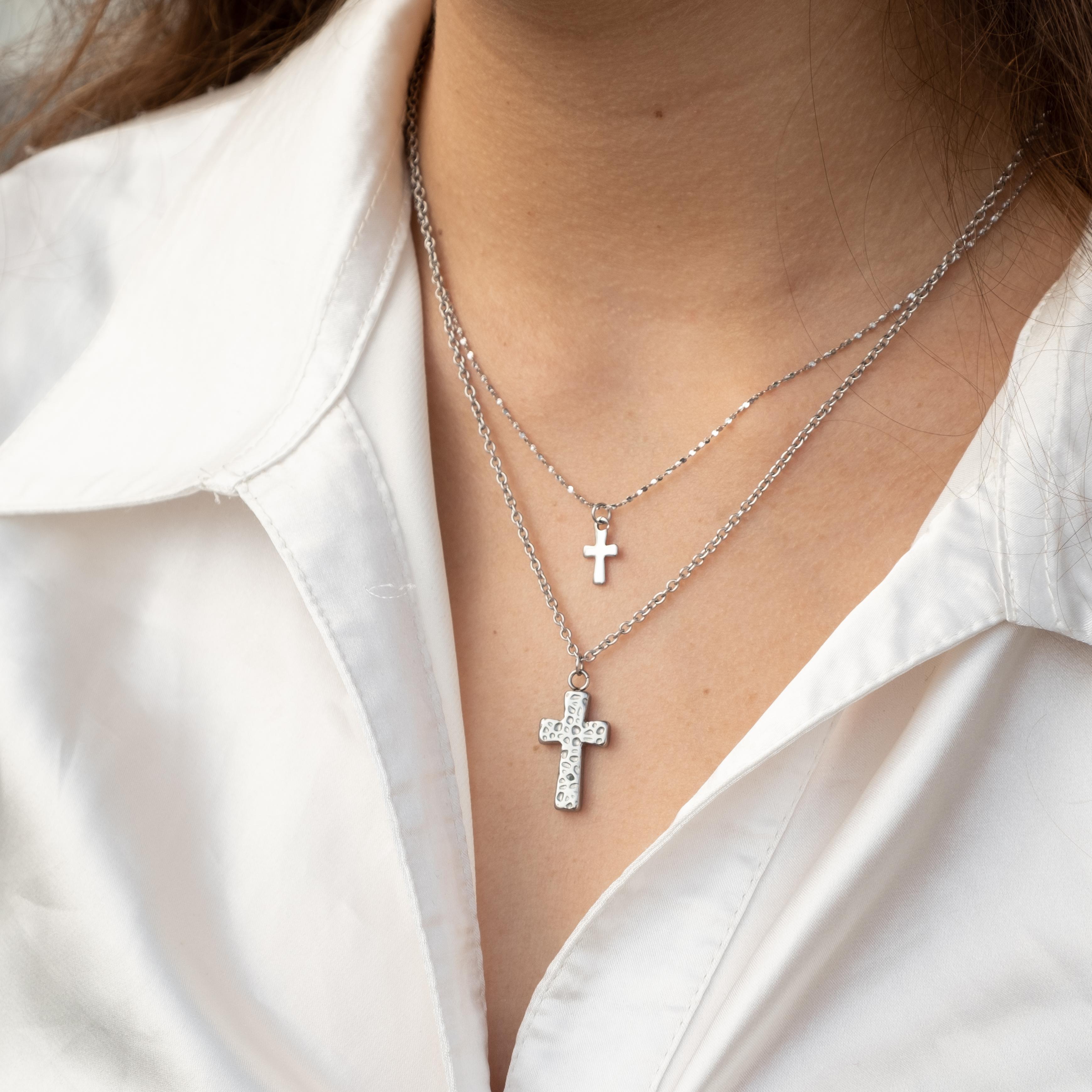 Vrouw met witte blouse met twee zilveren kettingen met kruisje