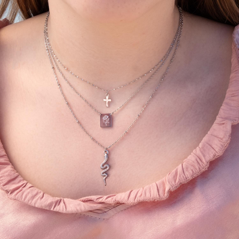 Vrouw draagt verschillende zilveren kettinkjes om de hals