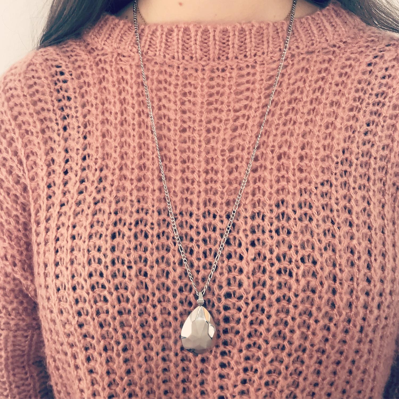 Meisje met roze trui draagt zilveren druppel ketting